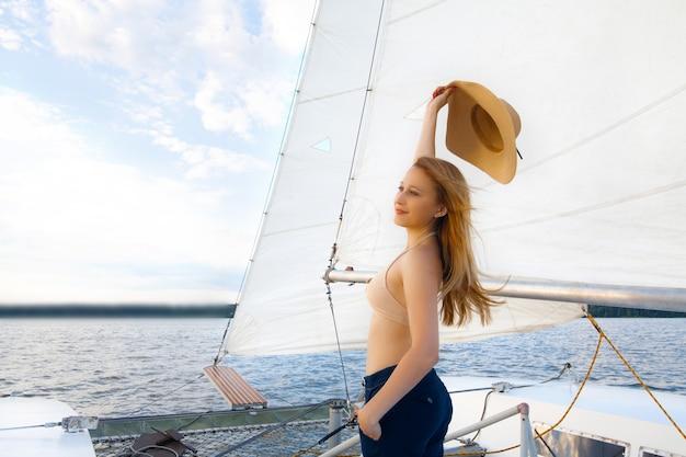 Uma mulher com um chapéu em um iate, contra o céu e o mar.