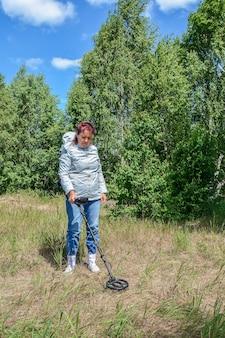 Uma mulher com um detector de metais procura artefatos em uma clareira na floresta