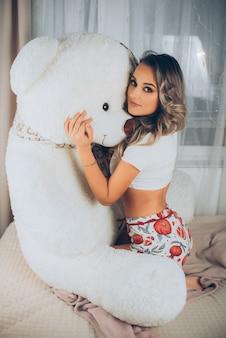 Uma mulher com um enorme ursinho de pelúcia na cama em um pijama sexy