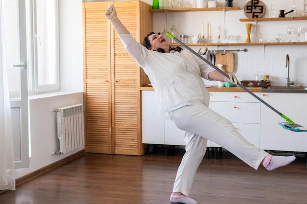 Uma mulher com um esfregão limpa a cozinha