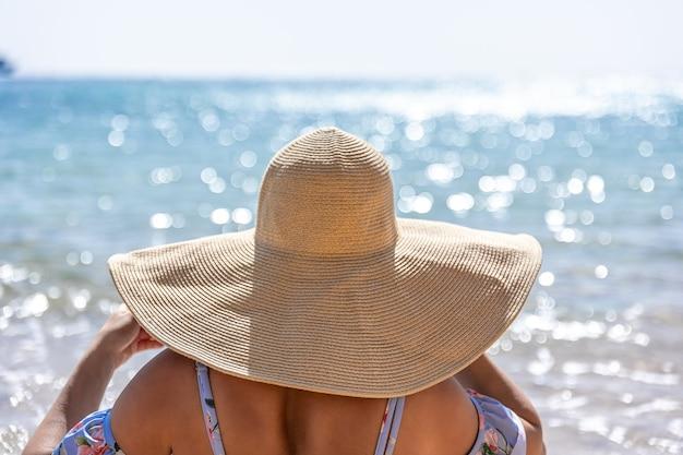 Uma mulher com um grande chapéu toma banho de sol na praia perto do mar.