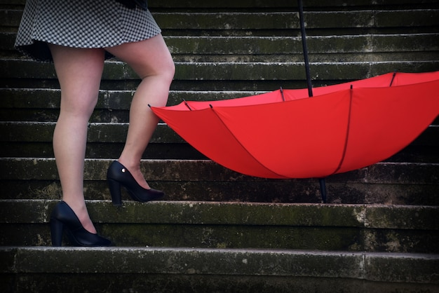 Uma mulher com um guarda-chuva vermelho