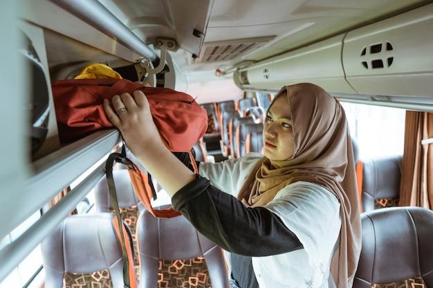 Uma mulher com um lenço na cabeça coloca sua bolsa em uma prateleira enquanto está de pé no ônibus