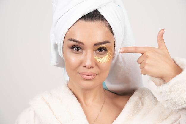 Uma mulher com um manto apontando para as manchas dos olhos.