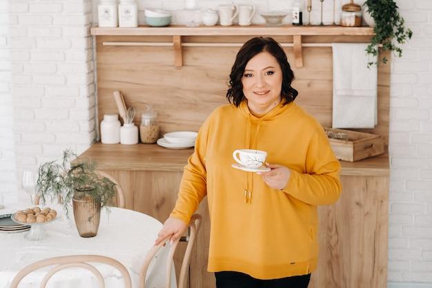 Uma mulher com um moletom laranja bebe café na cozinha de casa.