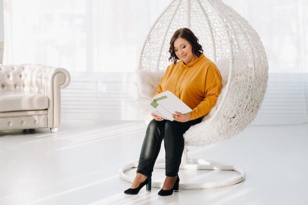 Uma mulher com um moletom laranja está sentada em uma cadeira incomum com um livro nas mãos.