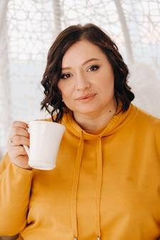 Uma mulher com um moletom laranja se senta em uma cadeira incomum e bebe café em casa.