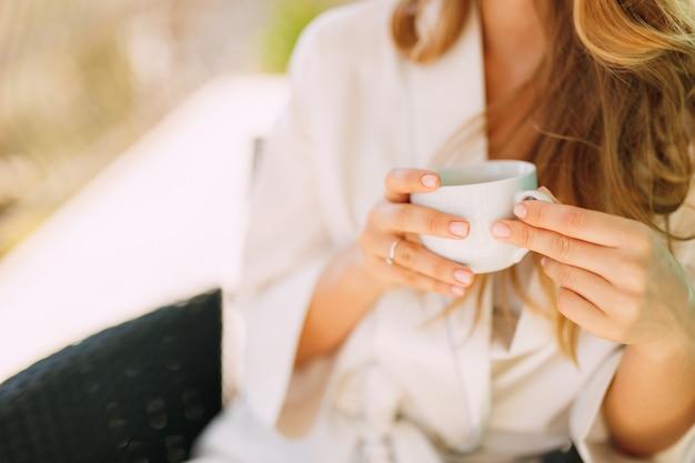 Uma mulher com um robe de manhã se senta em uma cadeira e segura uma xícara nas mãos