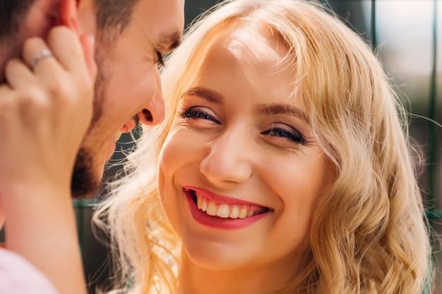 Uma mulher com um rosto bonito sorri genuinamente na lente da câmera e o cara ao lado dela