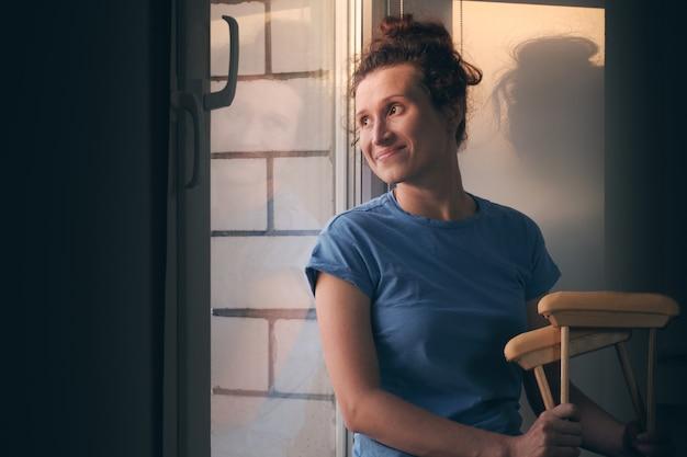 Uma mulher com um sorriso olha da janela do hospital