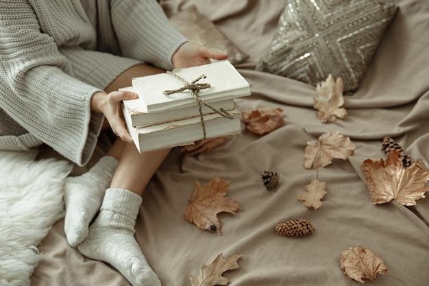 Uma mulher com um suéter de malha confortável está na cama com uma pilha de livros, clima de outono, fundo desfocado.