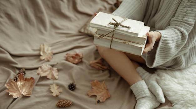 Uma mulher com um suéter de tricô aconchegante deitada na cama com uma pilha de livros