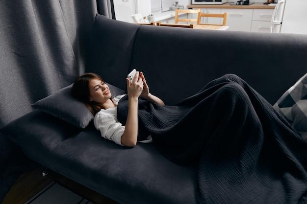 Uma mulher com um telefone celular deitada em um sofá cinza perto da janela ao fundo