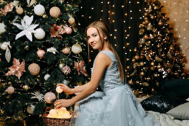 Uma mulher com um vestido azul noite está sentada perto de uma árvore de natal e sonha. muitas luzes e guirlandas de adorno de beleza