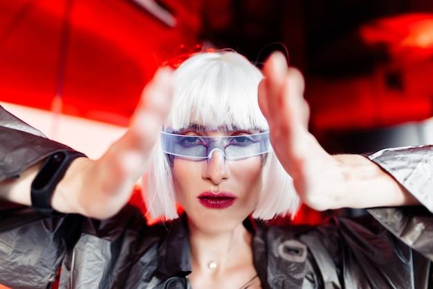 Uma mulher com um vestido futurista metálico com óculos olha em frente.