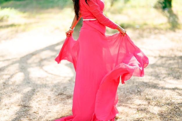 Uma mulher com um vestido rosa choque estiloso e saia longa está girando na grama seca e segurando as pontas