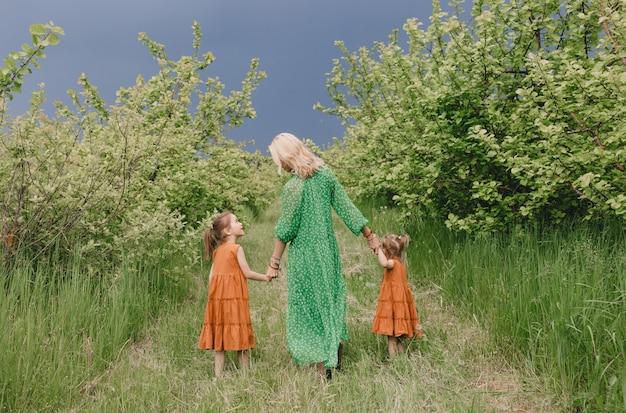 Uma mulher com um vestido verde caminha com duas meninas em um pomar de maçãs na primavera.