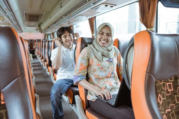 Uma mulher com um véu sorri enquanto usa um laptop e um jovem está sentado atrás dela usando fones de ouvido no ônibus