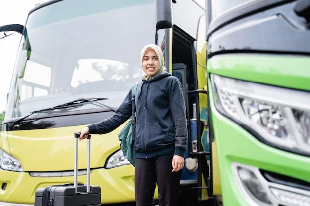 Uma mulher com um véu sorri olhando para a câmera enquanto segura uma mala do ônibus antes de sair