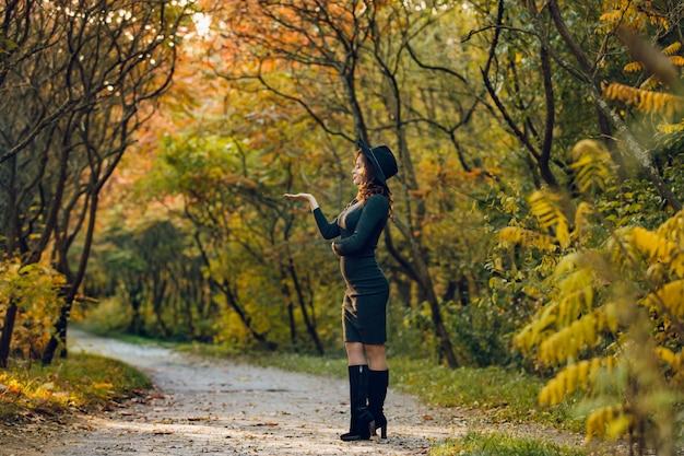 Uma mulher com uma bela figura em um chapéu preto fica para o lado no parque e posa para uma sessão de fotos