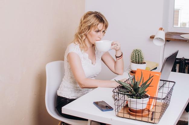 Uma mulher com uma blusa branca está sentada trabalhando em um laptop e bebe café ou chá
