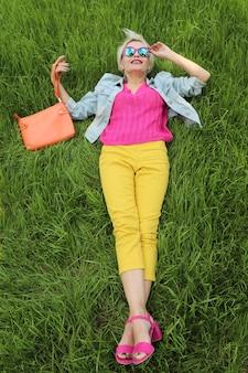 Uma mulher com uma bolsa está na grama verde com calças amarelas e uma jaqueta azul com sandálias