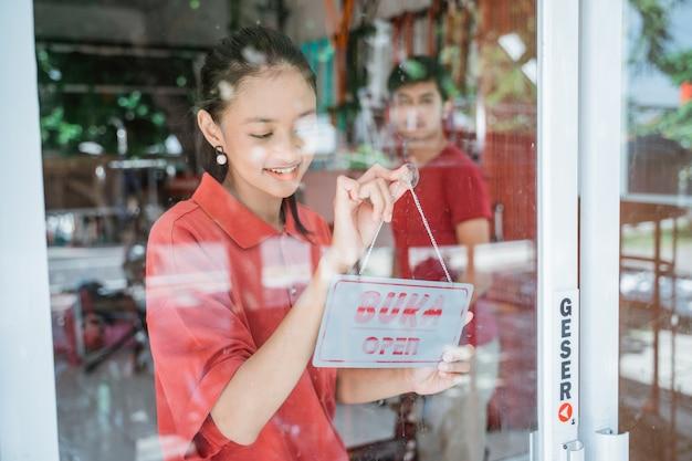 Uma mulher com uma camiseta vermelha se prepara para abrir uma loja, afixando uma placa de abertura na porta do para-brisa