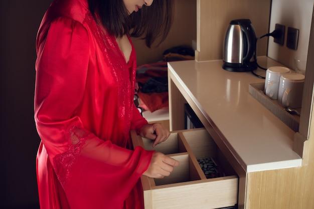 Uma mulher com uma camisola vermelha abre uma gaveta para encontrar algo na cozinha. não consigo encontrar, itens perdidos