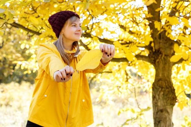 Uma mulher com uma capa de chuva amarela brilhante segura uma folha de outono amarela contra o fundo das folhas de outono amarelas. espaço livre para texto