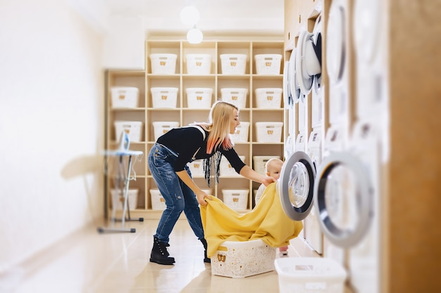Uma mulher com uma criança coloca os lençóis na lavanderia