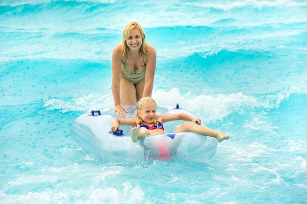 Uma mulher com uma criança em um círculo inflável de borracha brinca na piscina de um parque aquático de verão na chuva