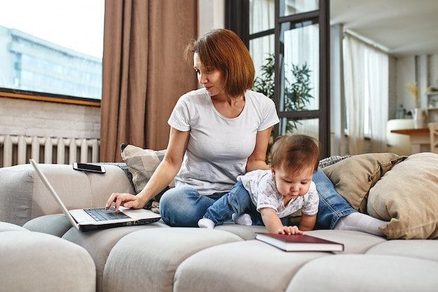 Uma mulher com uma criança em um laptop sentado em um sofá. trabalhar em casa, freelancer, trabalhar durante a licença de maternidade para acesso remoto.