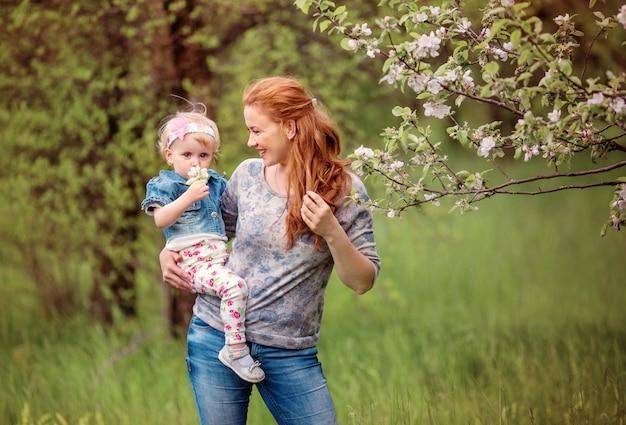 Uma mulher com uma criança nos braços perto da árvore de florescência. retrato de mãe e filha perto de uma árvore de florescência
