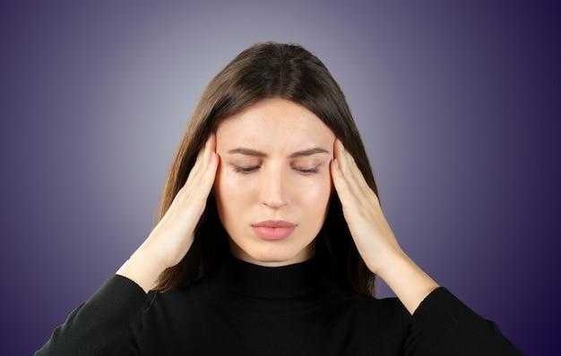 Uma mulher com uma dor na cabeça segura uma enxaqueca na cabeça