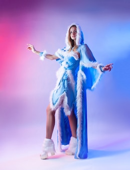 Uma mulher com uma fantasia de donzela de neve azul posa sobre um fundo de néon claro