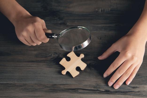 Uma mulher com uma lupa olha para uma peça de um quebra-cabeça