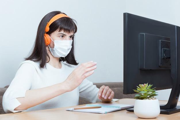 Uma mulher com uma máscara de proteção médica e fones de ouvido faz uma videochamada online e discute a situação de estar sentado a uma mesa no escritório