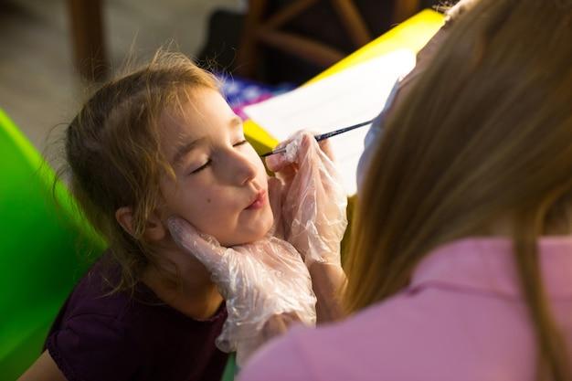 Uma mulher com uma máscara médica desenha um padrão de aquagrim no rosto de uma criança no estúdio em frente a um espelho com lâmpadas. diversão para as crianças - coloração facial. rússia, moscou, 15 de agosto de 2020