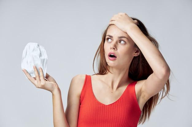 Uma mulher com uma máscara médica na mão levanta a cabeça e olha para o lado