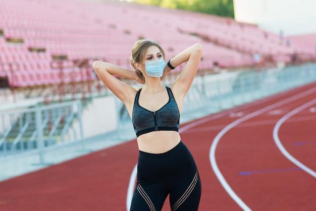 Uma mulher com uma máscara médica sozinha em um estádio vazio com assentos vermelhos. cancelamento de eventos esportivos durante o coronavírus.