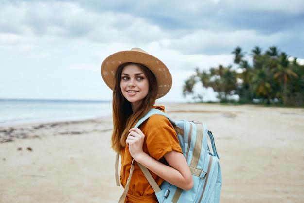 Uma mulher com uma mochila azul em um vestido amarelo e chapéu caminha ao longo do oceano ao longo da areia com palmeiras