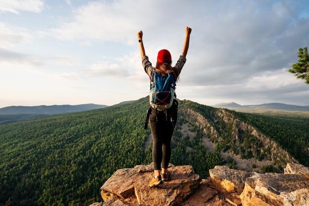 Uma mulher com uma mochila de pé no contexto das montanhas com as mãos levantadas, vista traseira. um homem nas montanhas levanta as mãos. um homem no fundo das montanhas. copie o espaço