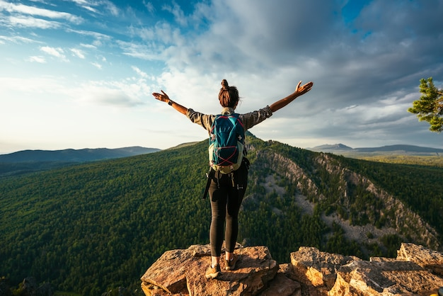 Uma mulher com uma mochila fica no topo de uma montanha com as mãos levantadas e admira a beleza de um vale de montanha, vista traseira. a garota viaja para lugares lindos. pôr do sol nas montanhas