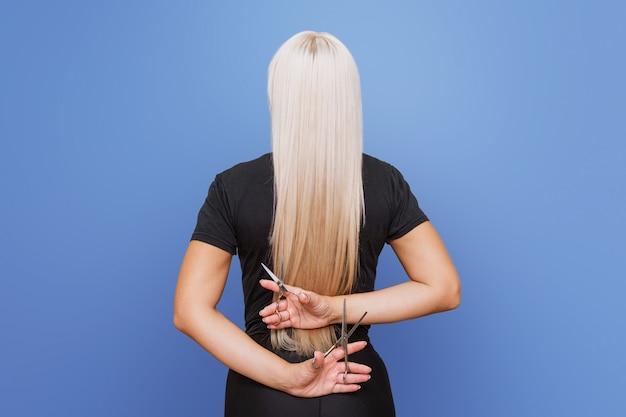 Uma mulher com uma tesoura recua e corta seus longos cabelos loiros. o conceito de um cabeleireiro profissional e cuidados com os cabelos