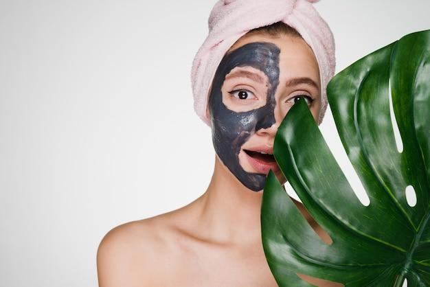 Uma mulher com uma toalha na cabeça aplica uma máscara de limpeza nas áreas problemáticas da pele