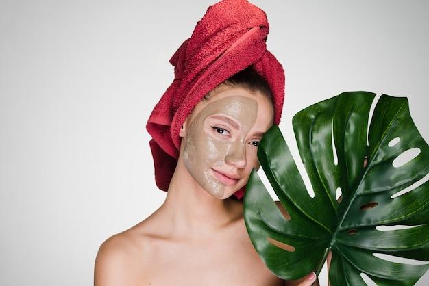 Uma mulher com uma toalha na cabeça aplicou uma máscara de limpeza no rosto