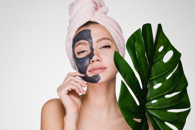 Uma mulher com uma toalha na cabeça após o banho coloca uma máscara no rosto e segura uma folha verde