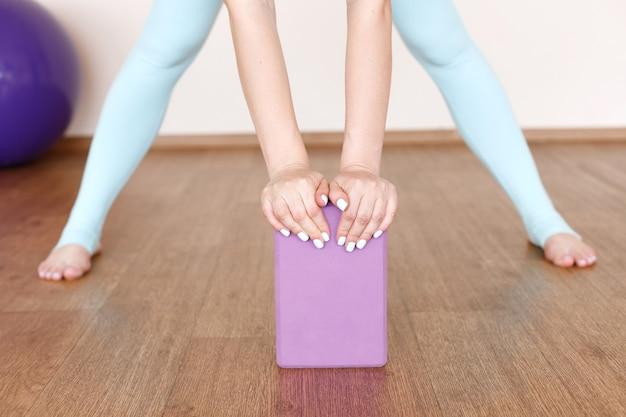 Uma mulher com uma xícara esportiva se espreguiça. ioga. fechar-se