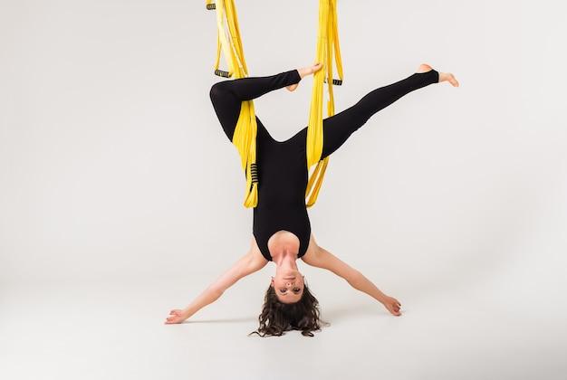 Uma mulher com uniforme esportivo faz uma pose invertida em uma rede. ioga antigravidade