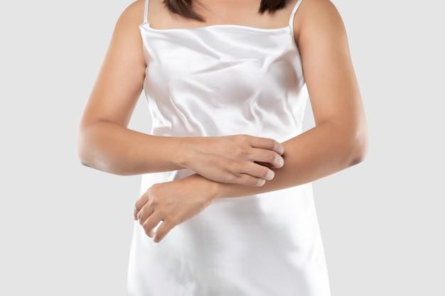 Uma mulher com vestido de cetim branco está coçando os braços devido a coceira em um vestido cinza